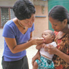 Health worker checking baby