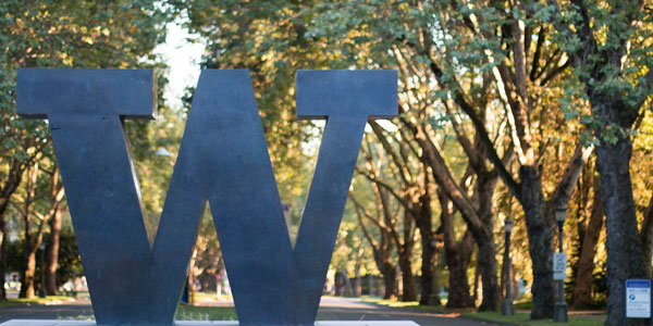 Bronze W in front of a corridor of trees in the fall