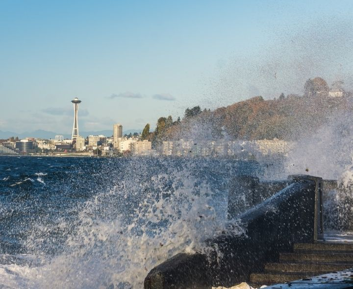Waves crashing, city in background