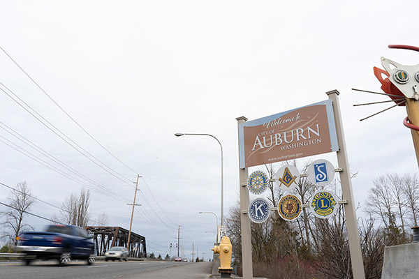 Sign for the city of Auburn in front of a train track