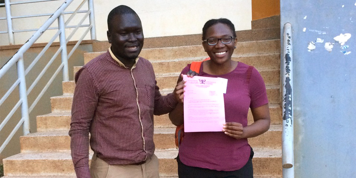 Aisha Abedi with co-author Dominic Ogwal holding their Uganda IRB approval certification letter