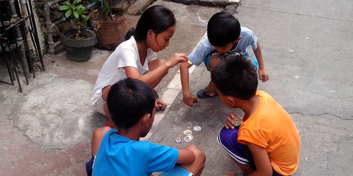 Filipino children playing pogs on the street [(CC by-SA 3.0) Jewel457]