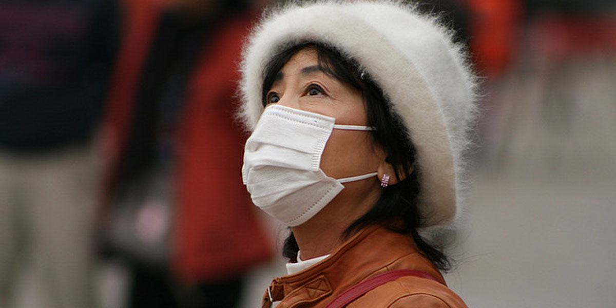 Woman in China wears face mask as protection against pollution in the air. [(CC BY-SA 2.0): Nicolò Lazzati]